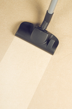 Vacuum Cleaner sweeping Brand New Carpet. Housework and home hygiene. photo