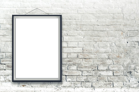 Blank vertical painting poster in black frame hanging on white brick wall. Painting proportions match international paper size A.
