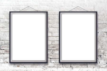 two piece: Two blank vertical painting poster in black frame hanging on white brick wall. Painting proportions match international paper size A. Stock Photo