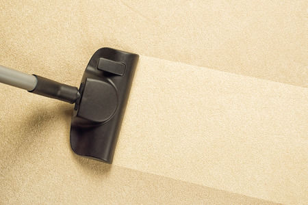Vacuum Cleaner sweeping Brand New Carpet. Housework and home hygiene. Stock Photo