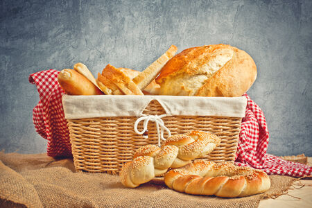 Delicious bread and rolls in wicker basket on kitchen table photo