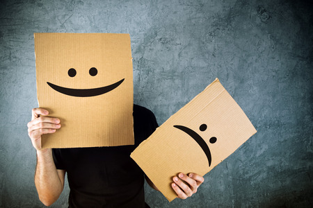 emoticons: Man holding cardboard paper with happy smiley face printed on. Happiness and joy concept.