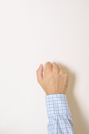 knocking: Male hand is knocking on wooden door, conceptual image. Visitor or guest is at the door. Stock Photo