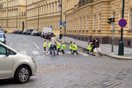 safety vest: PRAGUE, CZECH REPUBLIC - SEPTEMBER 06, 2014: Kindergarden children wearing yellow safety vests while crossing the street in Prague. Editorial