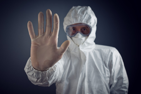 Medical Health Care Worker Showing Stop Sign with hand, entrance is forbidden in quarantine zone.