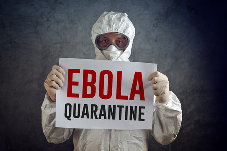 disease control: Ebola Quarantine sign held by medical healh care worker wearing protective gown, glowes, mask and goggles. Stock Photo