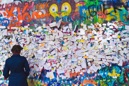 PRAGUE, CZECH REPUBLIC - SEPTEMBER 11, 2014: Woman looking at Famous John Lennon Wall on Kampa Island in Prague is filled with Beatles inspired graffiti and pieces of lyrics since the 1980s. Graffities are drawn on daily basis.