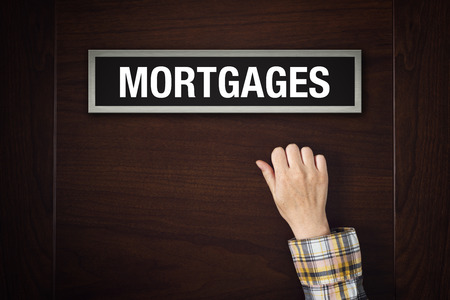 knocking: Female hand is knocking on Mortgages door, conceptual image. Stock Photo