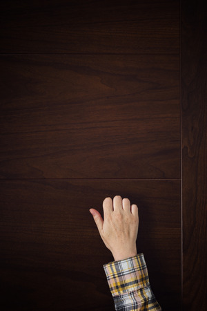lodger: Female hand is knocking on wooden door, conceptual image. Visitor or guest is at the door. Stock Photo