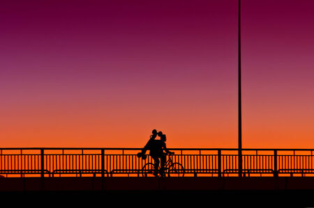 Silhouette of a man riding a bicycle over the bridge in susnet photo