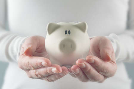 Woman Holding White Piggy Coin Bank, Home Budget and Finances concept. photo