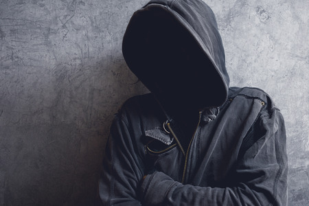 Faceless unknown and unrecognizable man with hood in dark room, spooky criminal person.