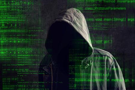 virus informatico: Faceless hacker anónimo capucha con código de programación desde el monitor