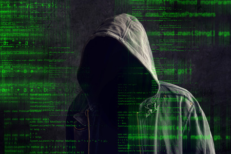 Faceless hooded anonymous computer hacker with programming code from monitor photo