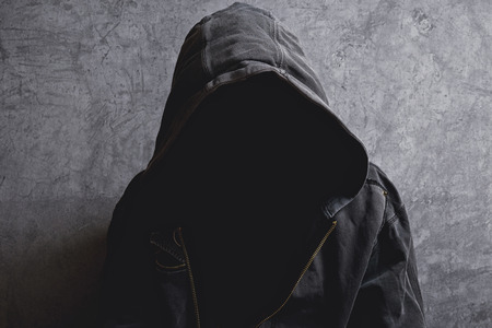 Faceless unknown and unrecognizable man withouth identity wearing hood in dark room, spooky criminal person. Фото со стока