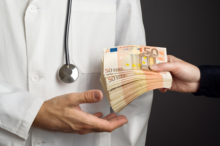 nepotism: Corruption in Health Care Industry, Doctor receivening large amount of Euro banknotes as a bribe.