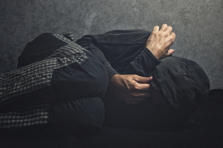 Drug Addict laying on the floor in agony, having an addiction crisis Stock Photo