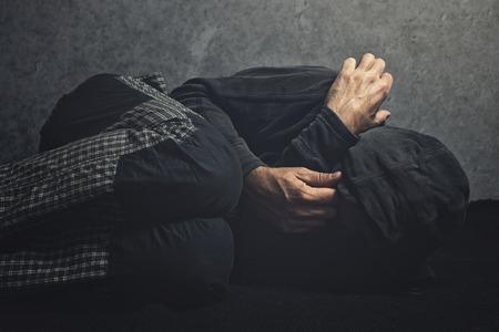 Drug Addict laying on the floor in agony, having an addiction crisis Фото со стока
