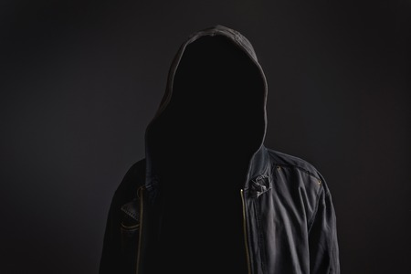 Faceless unknown and unrecognizable man withouth identity wearing hood in dark room, spooky criminal person. Banco de Imagens