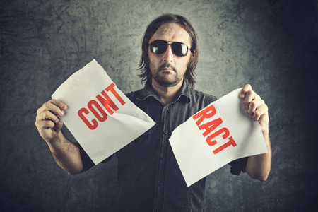 cancellation: Man tearing apart contract document paper as a gesture of agreement cancellation. Stock Photo