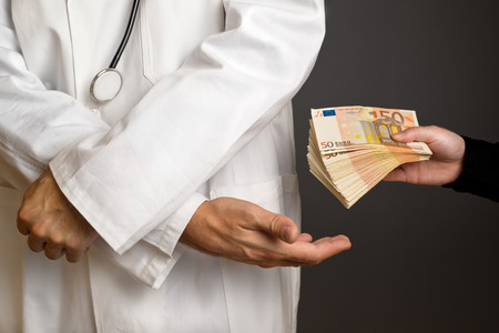 Corruption in Health Care Industry, Doctor receivening large amount of Euro banknotes as a bribe.