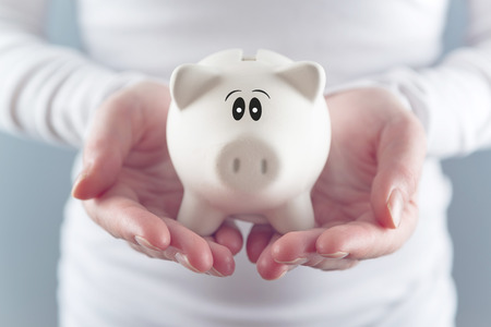 secure money: Woman holding piggy coin bank in hands, selective focus with shallow depth of field