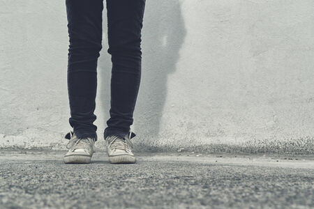 reckon: Legs of Young adult woman in black pants and white sneakers standing on the street. Stock Photo