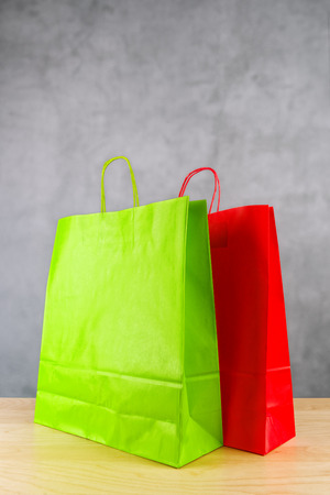 extravagance: Green And Red Paper Shopping Bags on Wooden Retail Store Table. Stock Photo