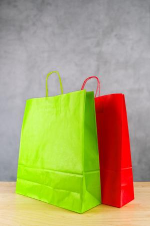compras compulsivas: Verde y rojo de papel bolsas de la compra en el vector de madera Retail Store.