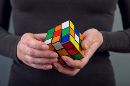 NOVI SAD, SERBIA - NOVEMBER 17, 2014: Woman solving Rubiks Cube invented by a Hungarian architect Erno Rubik in 1974 is famous is 3 dimensional puzzle originally called Magic Cube.