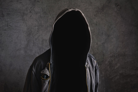 Faceless unknown and unrecognizable man without identity wearing hood in dark room, spooky criminal person. photo