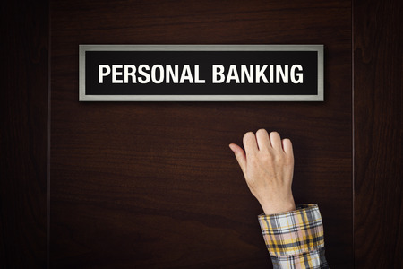 personal banking: Female hand is knocking on Personal Banking door, conceptual image