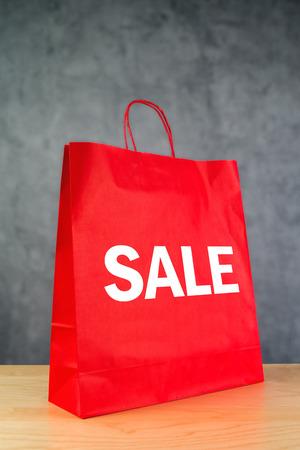 compras compulsivas: Venta de separaci�n de papel bolsa de color rojo sobre tabla de madera de Retail Store. Foto de archivo