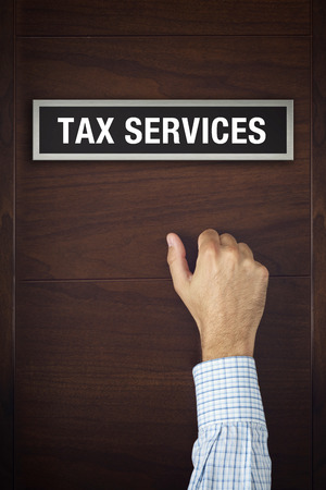 knocking: Male hand is knocking on tax services door, conceptual image. Stock Photo