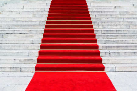 Red carpet on staircase marking the route taken by celebrities on ceremonial events Stock Photo