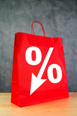 shopaholism: Discount Percentage Symbol on Red Shopping Bag on Wooden Retail Store Table. Stock Photo