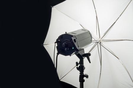 studio photography: Photography Studio Flash Head with Umbrella and dark black copy space.