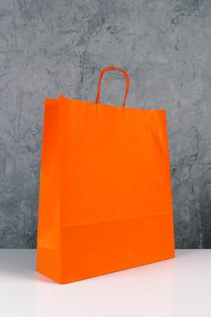 compras compulsivas: Papel Bolsa de la compra de naranja en el vector de madera Retail Store.