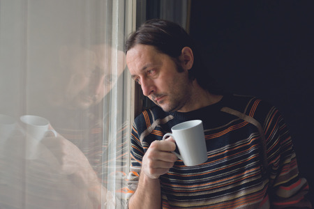 depresi�n: Triste solamente mediados de hombre adulto de pie junto a la ventana y el consumo de caf�, buscando alg�n lugar en la distancia.