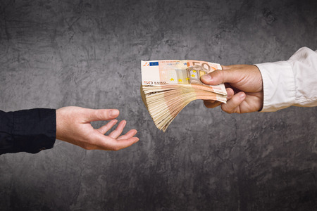 Give: Money Loan. Bank officer loaning stack of euro banknotes money.