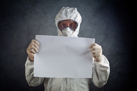Medical healh care worker wearing protective gown, gloves, mask and goggles and holding blank paper as copy space.