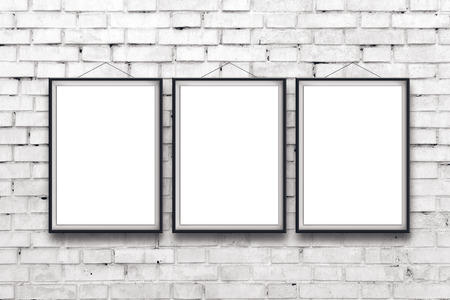 Three blank vertical painting poster in black frame hanging on white brick wall. Painting proportions match international paper size A.