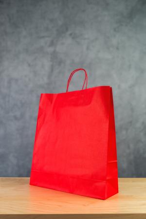 compras compulsivas: Bolsa de compras de papel rojo sobre tabla de madera de Retail Store. Foto de archivo