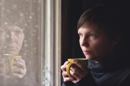 reflexion: Lonelsome mujer de beber una taza de café junto a la ventana de su sala de estar, mirando la nieve que cae con una mirada triste en su rostro. Enfoque selectivo con profundidad de campo.