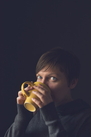 Beautiful caucasian adult woman drinking cup of coffee in dark room. Selective focus with shallow depth of field.