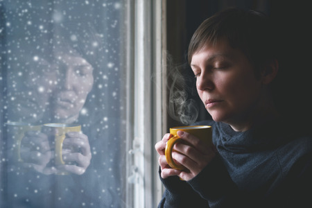 lonesome: Lonelsome woman drinking cup of coffee by the window of her living room while the snow is falling outside. Selective focus with shallow depth of field. Stock Photo