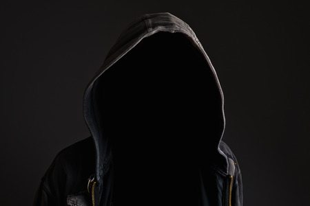 hidden danger: Faceless unknown and unrecognizable man without identity wearing hood in dark room, spooky criminal person.