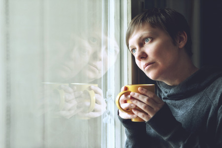 Lonely woman drinking cup of coffee by the window of her living room, looking out with a sad look on her face. Selective focus with shallow depth of field.
