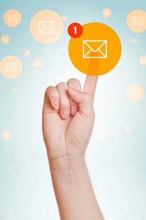 inbox: Checking E-mail Inbox, caucasian female hand pushing e-mail icon on virtual display. Stock Photo