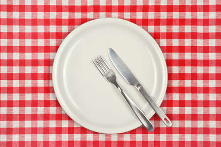 checker plate: Empty plate on restaurant table with red and white checkered tablecloth